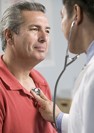 Doctor listening to man's chest with stethoscope.