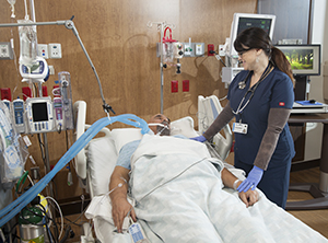 Healthcare provider caring for intubated man in intensive care unit bed.