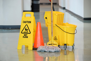 Yellow caution wet floor sign and yellow mop bucket.