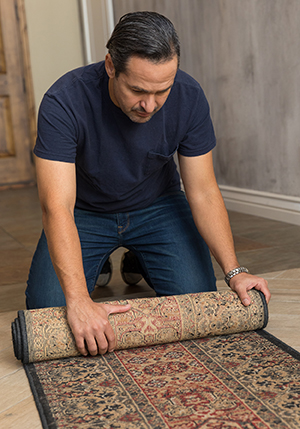 Man rolling up area rug.
