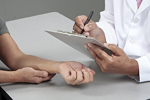 Healthcare provider writing on clipboard while patient rests arm on table.