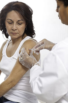 Woman getting a shot in her upper arm